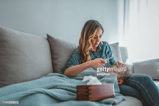 mother is checking her son temperature - fever stock pictures, royalty-free photos & images