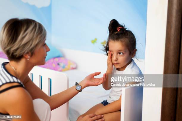 mother is comforting her sad little daughter - moms crying in bed stock photos and pictures