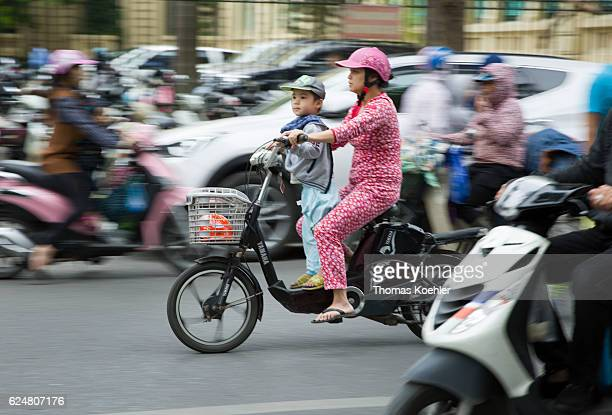 A mother is driving with her son on a moped in the street traffic of Hanoi The child does not wear a protective helmet on October 30 2016 in Hanoi...
