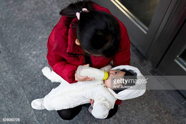 mother is feeding a baby outdoors - japanese breastfeeding stock pictures, royalty-free photos & images