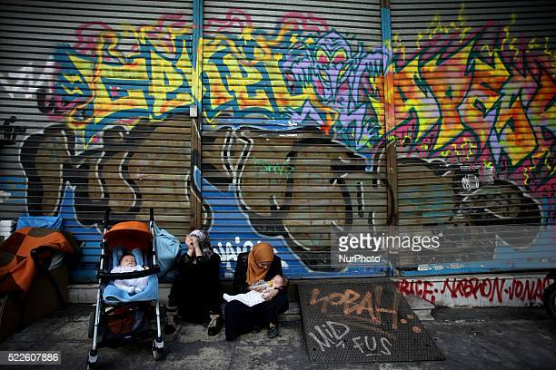 A mother is feeding her baby Refugees sitting in front of a graffiti in Athens city center April 15 2016