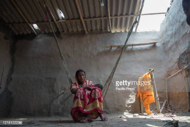 A mother is feeding her child under the broken roof of her own house which has been broken due to the super cyclone Amphan