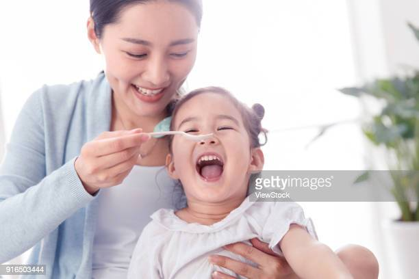 Mother is feeding the girl