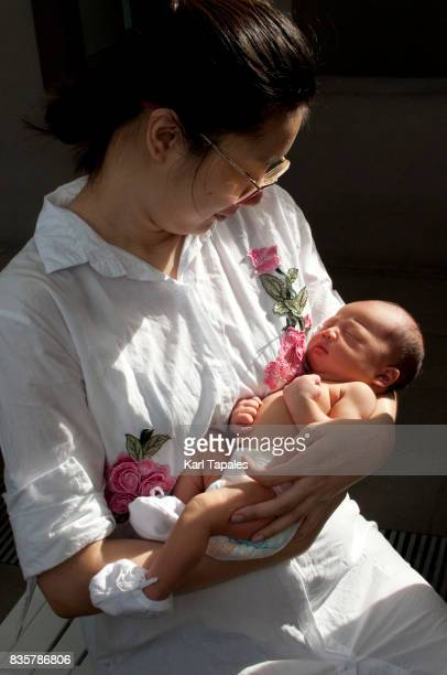 A mother is holding a newborn baby