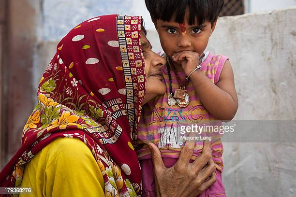 CONTENT] A mother is holding her child with care and tenderness in a street of Vrindavan Uttar Pradesh India