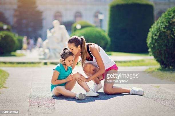 mother is hugging and kissing her injured runner daughter fallen on the ground - leg kissing stock photos and pictures