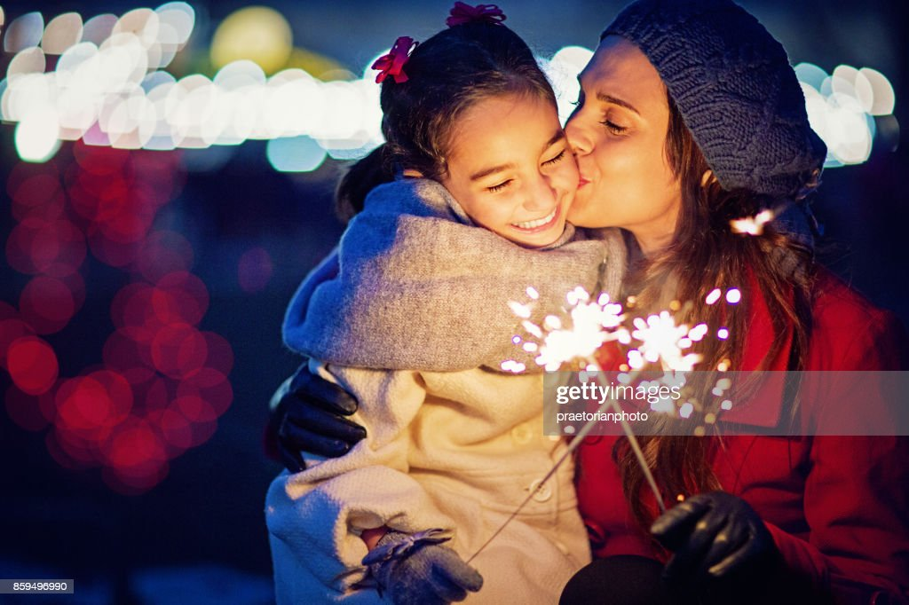 Mother is kissing her daughter at Christmas : Stock Photo