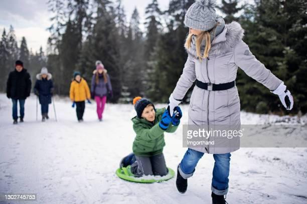 母親在冬天把兒子拉上雪橇 - 跟拍鏡頭 個照片及圖片檔