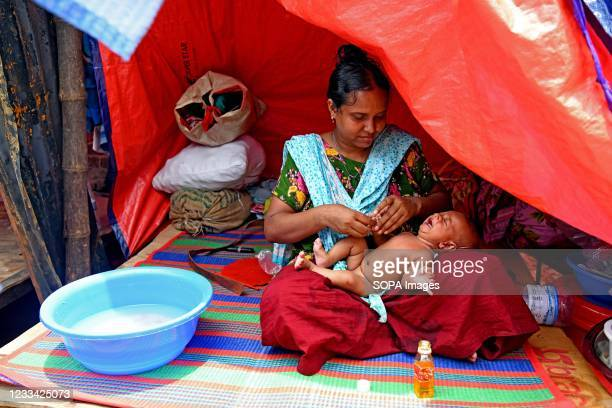Mother is seen bathing her child in Sat tala slum. According to World Bank, each year up to half a million rural migrants stream into the capital...