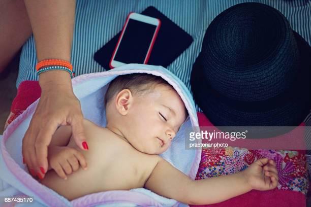 Mutter ist ihr schlafendes Baby unter dem Sonnenschirm streicheln.