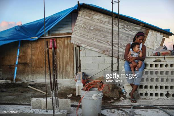 Mother Isamar holds her baby Saniel, 9 months, at their makeshift home, under reconstruction, after being mostly destroyed by Hurricane Maria, on...