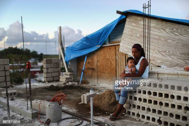 Mother Isamar holds her baby Saniel 9 months at their makeshift home under reconstruction after being mostly destroyed by Hurricane Maria on December...