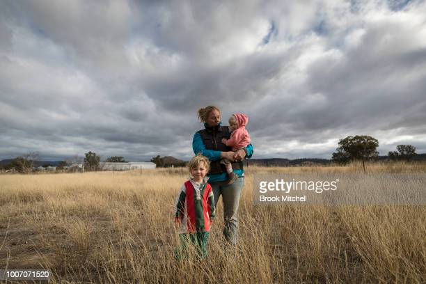 Mother Jessica Taylor with Bony 18 months and Charlie on their farm outside Coonabarabran The family is has battled through almost two years without...