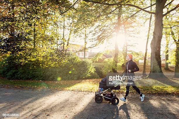 Mother jogging with baby stroller on road against trees at park