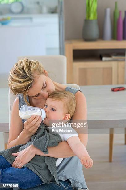 Mother kisses and bottle feeds baby