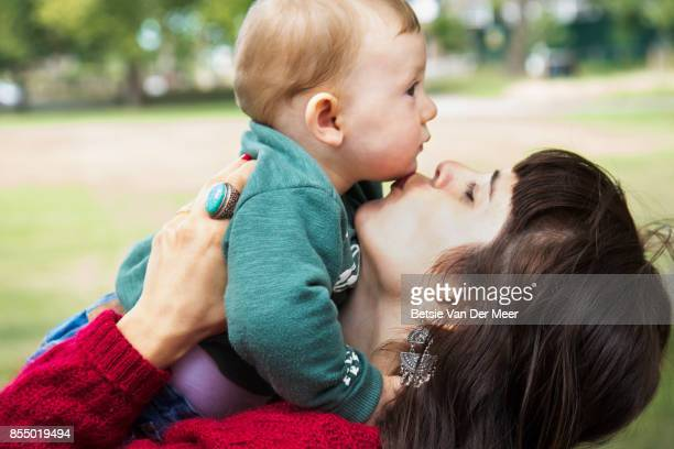 Mother kisses her young  baby son standing in urban park.