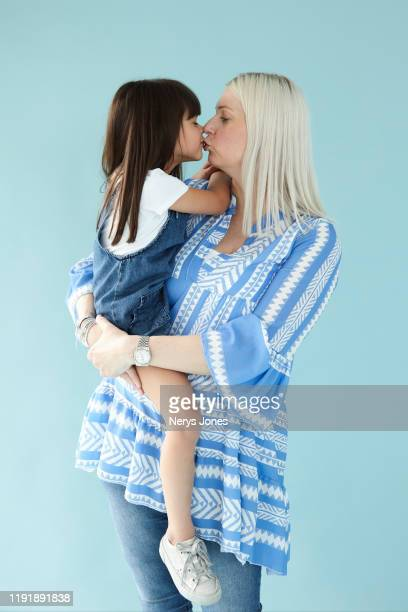 mother kissing and carrying her child against pale blue background - nerys jones stock photos and pictures