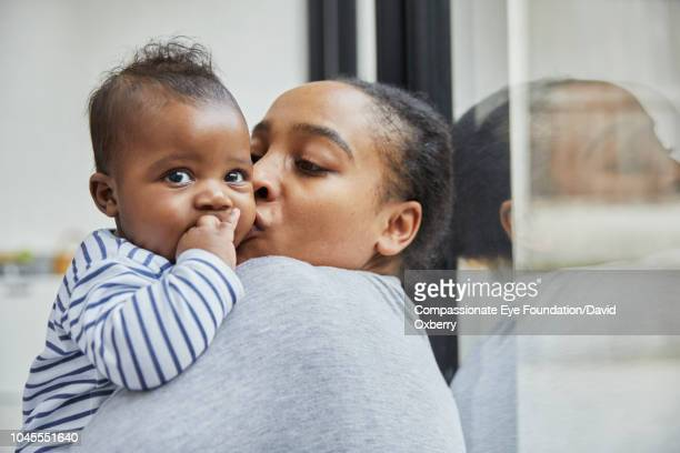 Mother kissing baby boy by window