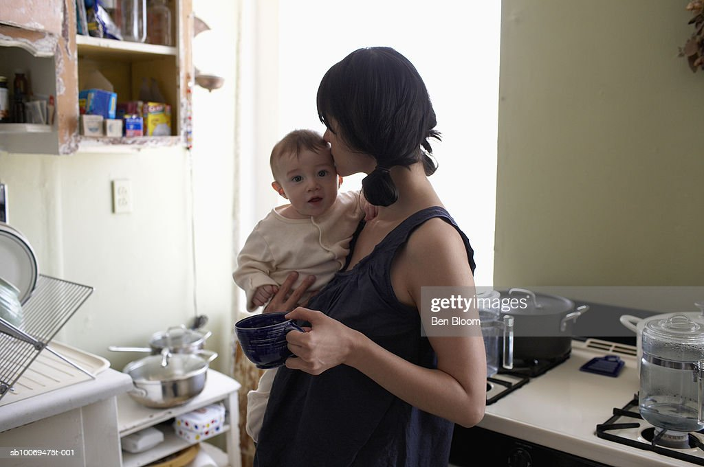 Mother kissing baby boy (6-11months) in kitchen : Stock Photo