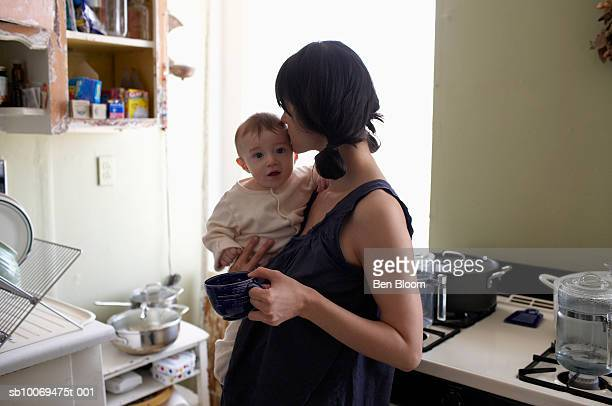 mother kissing baby boy (6-11months) in kitchen - 6 11 months stock pictures, royalty-free photos & images