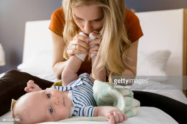 mother kissing baby boy's feet - kissing feet stock pictures, royalty-free photos & images