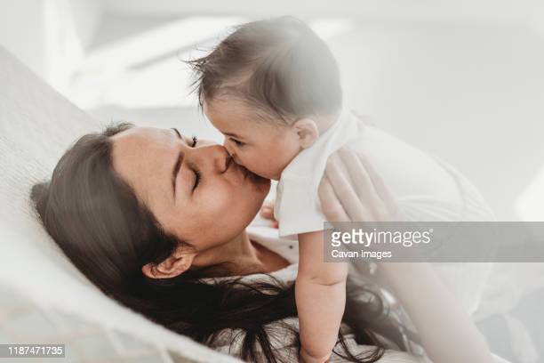 mother kissing baby daughter hammock in natural light studio - babyhood stock pictures, royalty-free photos & images