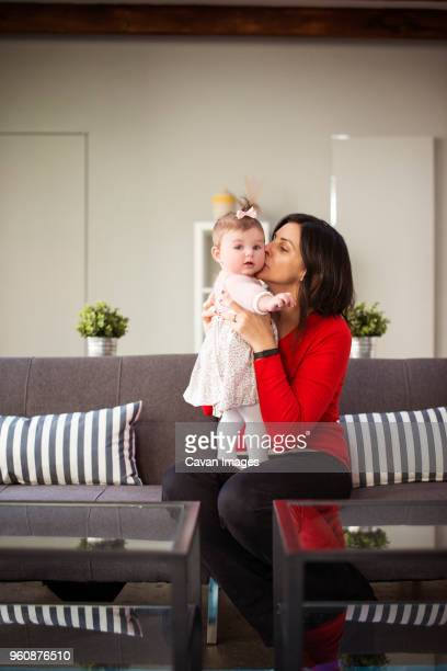 Mother kissing baby daughter while sitting on sofa at home