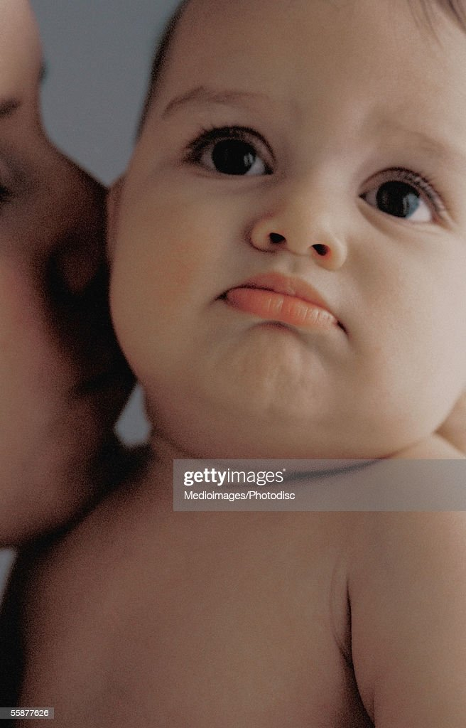 Mother kissing baby girl (3-6 months), close up : Stock Photo