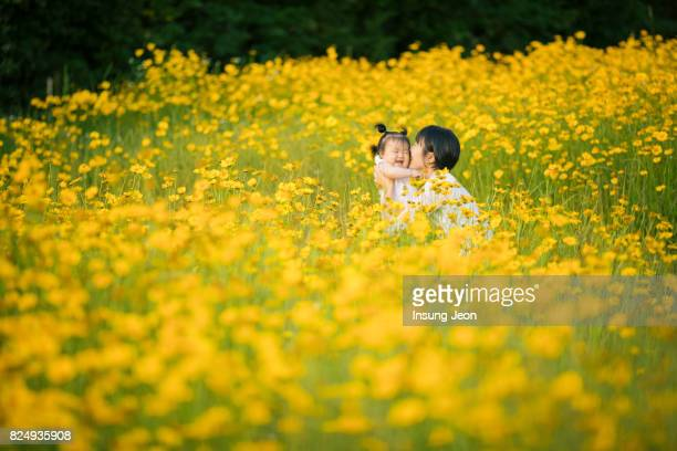 Mother kissing baby girl in yellow flower field