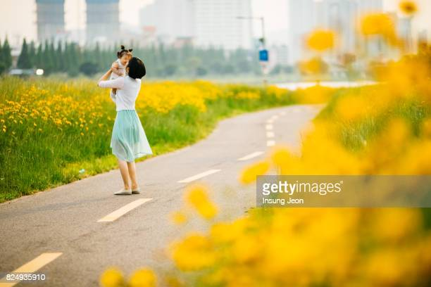 mother kissing baby girl in yellow flower field - indian girl kissing stock photos and pictures