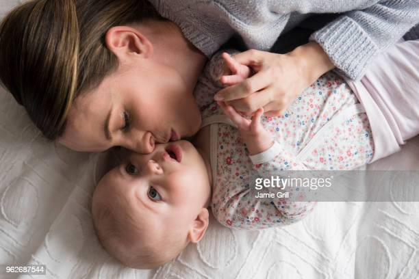 Mother kissing baby girl (18-23 months) with care
