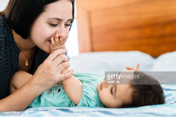 Mother kissing baby hand.