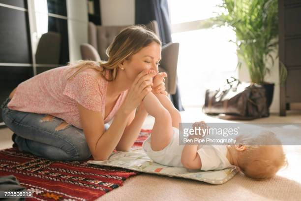 Mother kissing baby on rug
