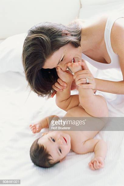 Mother kissing baby's feet on bed