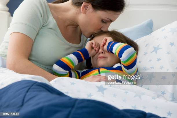 mother kissing crying son - good night kiss stock pictures, royalty-free photos & images