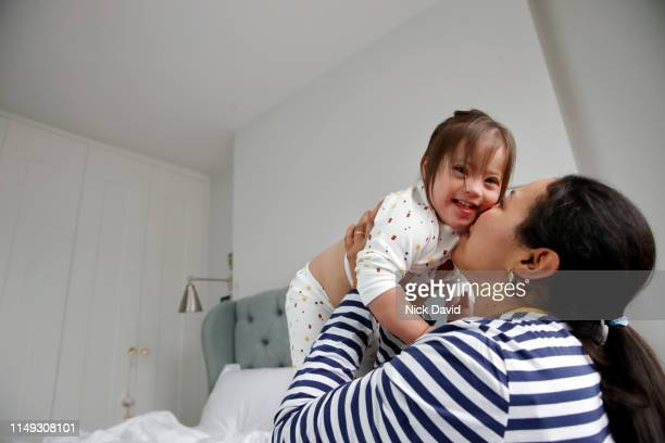 mother kissing cute toddler daughter in bedroom - parenting stock pictures, royalty-free photos & images