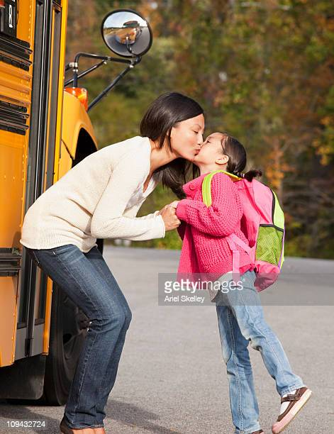 Mother kissing daughter as she gets on school bus