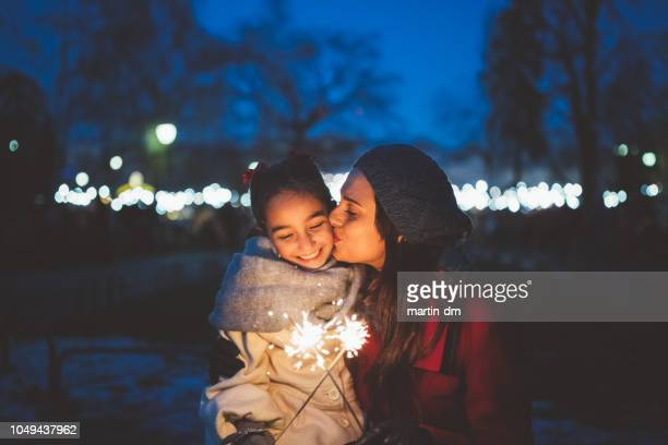 mother kissing daughter at christmas night - sparkler stock pictures, royalty-free photos & images