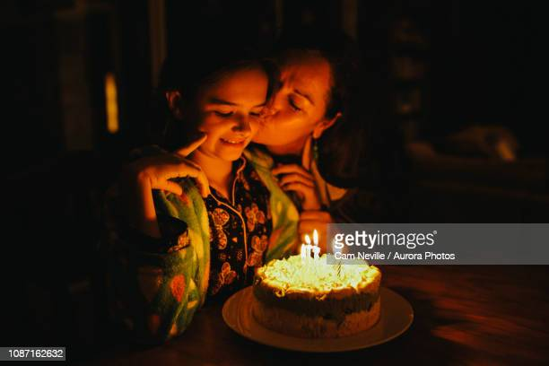 Mother kissing daughter during birthday