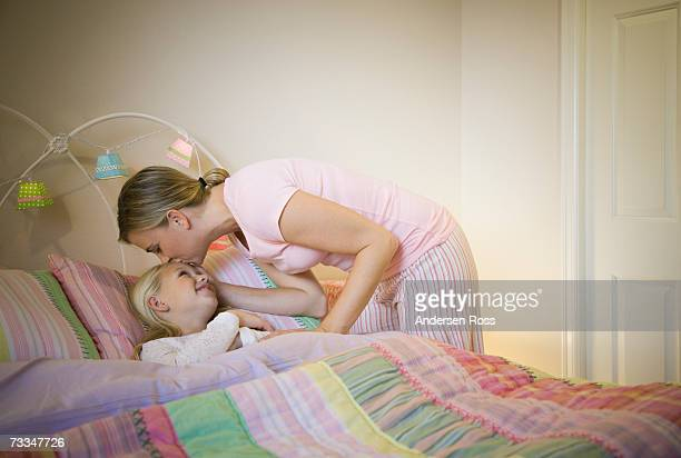 Mother kissing daughter (8-9) goodnight in bed