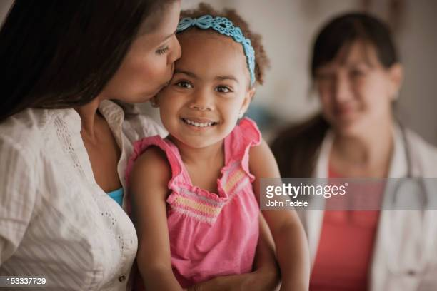 Mother kissing daughter in doctor's office