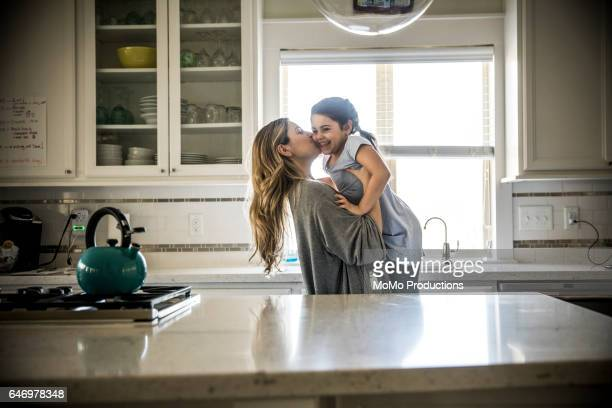 mother kissing daughter (7yrs) in kitchen - 6 7 years photos stock photos and pictures
