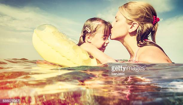 Mother kissing daughter in sea