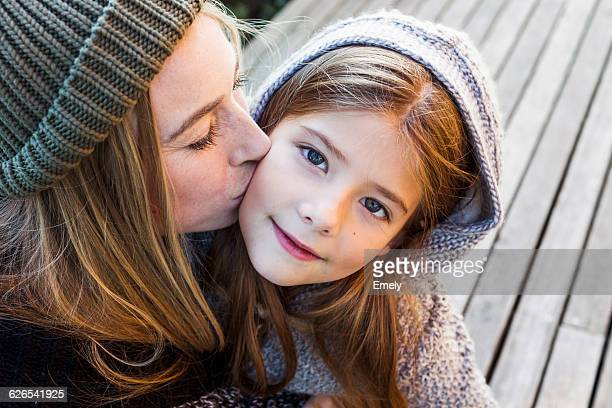 Mother kissing daughter on cheek, high angle portrait