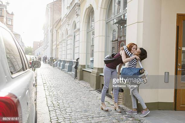 Mother kissing daughter on sidewalk against building in city