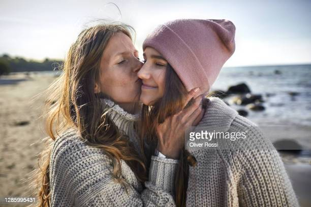 mother kissing daughter on the beach - tochter stock-fotos und bilder