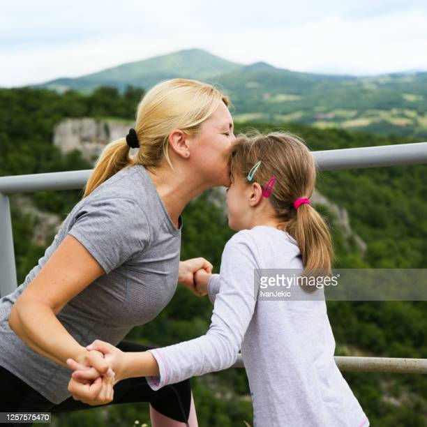 mother kissing daughter on the mountain - ivanjekic stock pictures, royalty-free photos & images