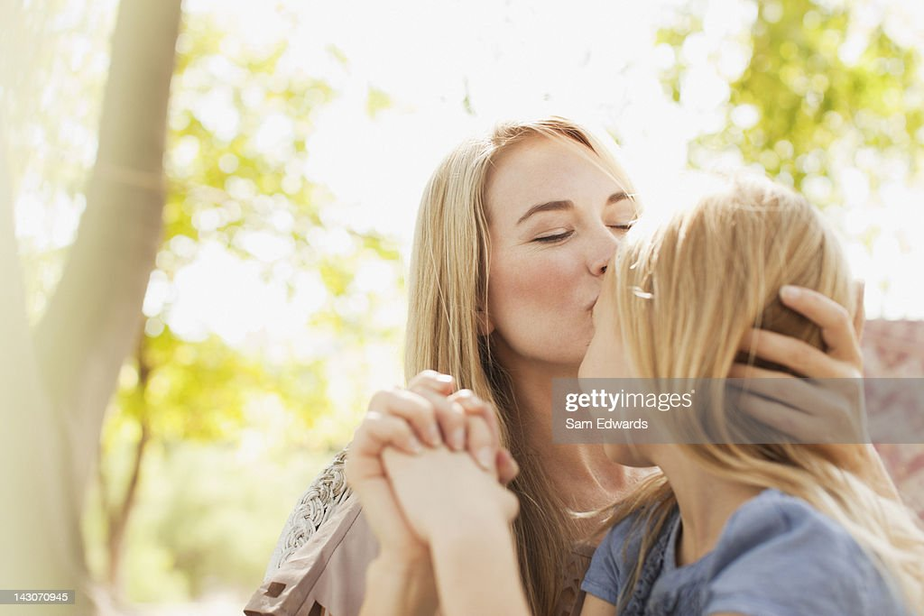 Mother kissing daughter outdoors : Stock Photo