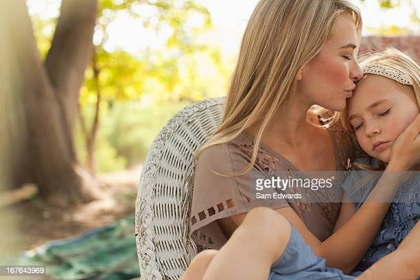 Mother kissing daughter outdoors