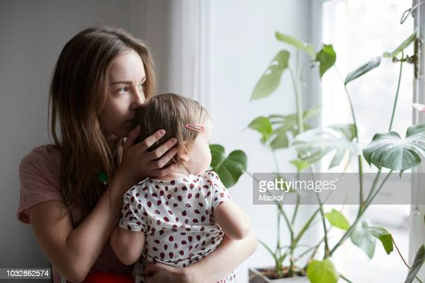 mother kissing daughter while looking through window at home - contemplation family stock pictures, royalty-free photos & images